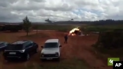 In this still made from an undated video provided by 66.ru, an explosion is seen after a helicopter fired a rocket in Luzhsky range, St. Petersburg region, Russia. A Russian military helicopter gunship accidentally fired on spectators during war games in western Russia, injuring several people, news reports said Sept. 19, 2017.