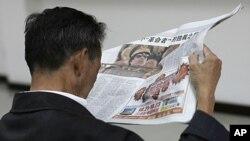 图为中国上海某公司一名男子10月21日正在阅读有关卡扎菲的报道