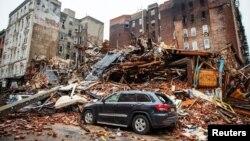 Sebuah mobil terlihat berada di antara puing-puing bangunan yang hancur pasca ledakan yang menghancurkan empat bangunan apartemen di New York, 27 Maret 2015 (REUTERS/Nancy Borowick/Pool).