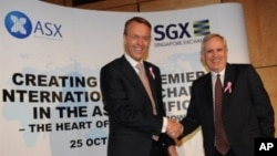 Magnus Bocker (L), CEO of the Singapore Exchange (SGX), shakes hands with Robert Elstone (R), CEO of the Australian Stock Exchange (ASX), in Sydney, 25 Oct 2010