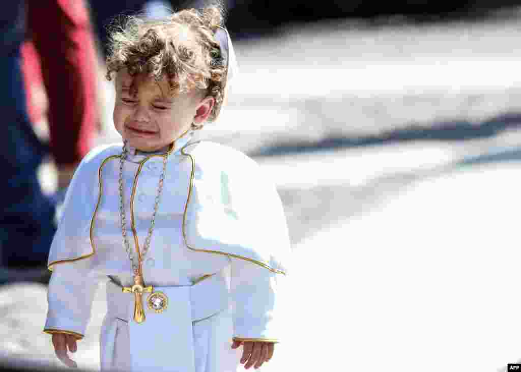 A child dressed as a Pope cries during the weekly Angelus prayer at St. Peter's square in the Vatican.