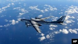 FILE - A British Royal Air Force photo shows a Russian long-range bomber flying in international airspace, Oct. 29, 2014.