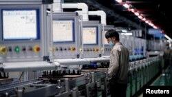 中国安徽合肥一家生产电动汽车电池的工厂工人在生产线上。(2021年3月30日)