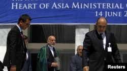 Afghan President Hamid Karzai (C) arrives for a group photo with ministers from other Heart of Asia member countries at the end of a conference in Kabul June 14, 2012.
