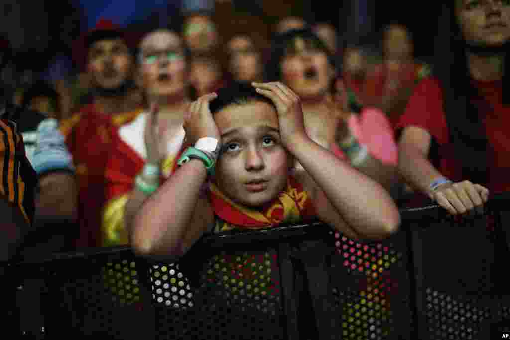 A Spanish soccer fan holds her head as she watches, on a giant display, the World Cup soccer match between Spain and Chile, in Madrid, Spain, June 18, 2014.
