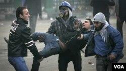 Manifestantes cargan a un colega herido durante choques cerca de la Plaza Tahrir.