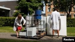 Ilmuwan Belgia Marjolein Vanoppen dan Sebastiaan Derese (kanan) menunjukkan cara menggunakan mesin bertenaga surya untuk mengubah air seni menjadi air minum dan pupuk di kampus University of Ghent, Belgia (26/7). (Reuters/Francois Lenoir)