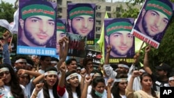 Members of a Kashmiri youth group hold posters of young rebel leader Burhan Wani, killed by Indian troops last year, while chanting anti-Indian slogans during a rally to mark the first anniversary of his death, in Lahore, Pakistan, July 8, 2017.