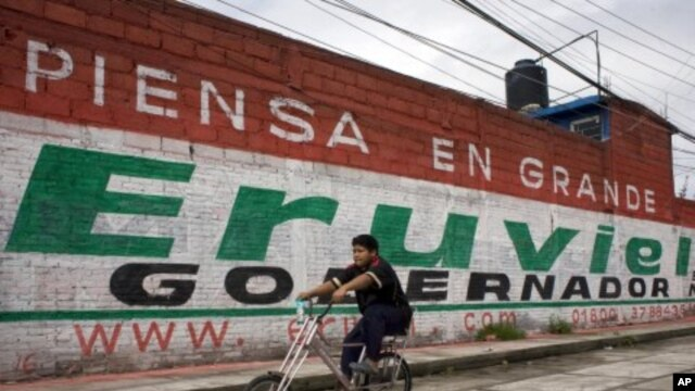 A cyclist rides past a mural for Eruviel Avila, candidate for governor of the state of Mexico for the Institutional Revolutionary Party (PRI) in Toluca, July 2, 2011