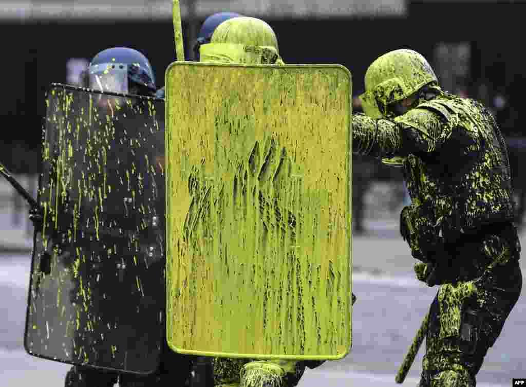 ប៉ូលិសកុបកម្មមានថ្នាំពណ៌នៅលើខ្លួន នៅក្នុងពេលប៉ះទង្គិចមួយជាមួយនឹងបាតុករ ដែលជាផ្នែកមួយនៃបាតុកម្មអាវលឿង (Yellow vests) ប្រឆាំងនឹងការឡើងថ្លៃប្រេង និងចំណាយរស់នៅក្នុង នៅលើផ្លូវ Champs Elysees ក្នុងក្រុងប៉ារីស ប្រទេសបារាំង កាលពីថ្ងៃទី១ ខែធ្នូ ឆ្នាំ២០១៨។
