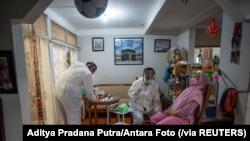Para petugas kesehatan bersiap melakukan tes usap kepada seorang warga di tengah lonjakan kasus COVID-19, di Bogor, 7 Juli 2021. (Foto: Aditya Pradana Putra/Antara Foto via Reuters)