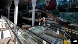 An employee walks off an escalator at a closed mall in Caracas, Venezuela, Feb. 10, 2016.