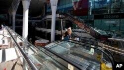 An employee walks off an escalator at a closed mall in Caracas, Venezuela, Feb. 10, 2016.