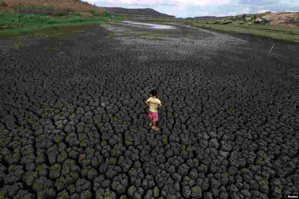 Natan Cabral, 5, stands on the cracked ground of the Boqueirao reservoir in the Metropolitan Region of Campina Grande, Paraiba state, Brazil.