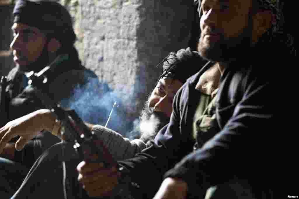 16일 시리아 알레포 지역에서 담배를 피며 휴식을 취하는 반군 병사들.