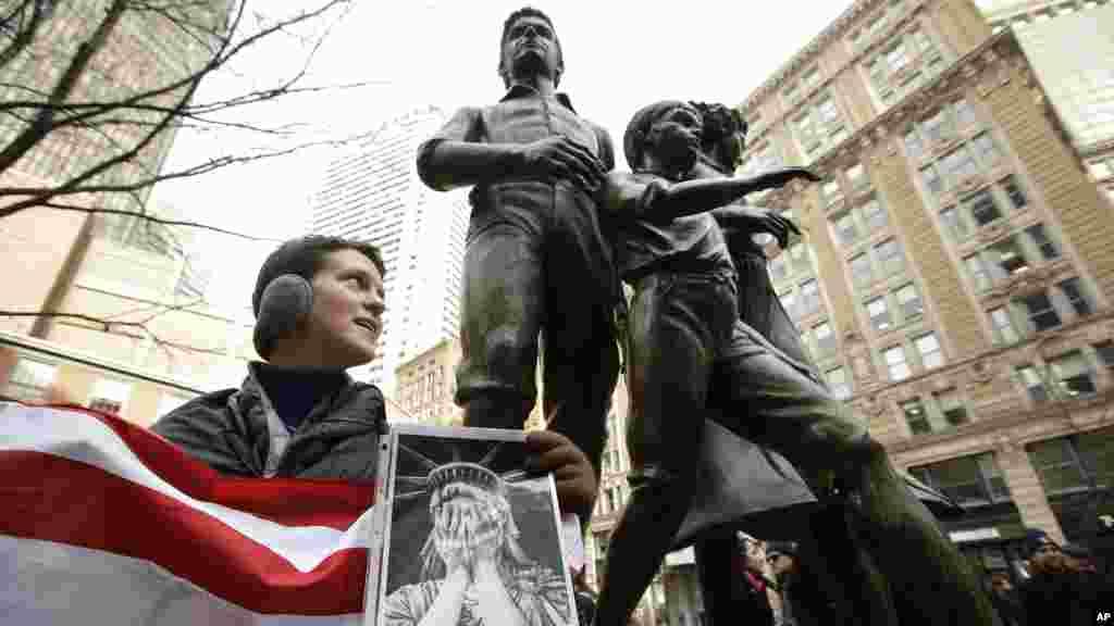 """Molly Hitt, avec un drapeau américain lors des protestation à Boston appelé """"We Will Persist"""" en français """"Nous persisterons"""", le 21 février 2017."""