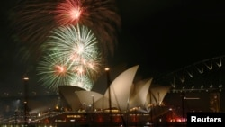 FILE - Fireworks explode over the Sydney Opera House in a display before the midnight fireworks that will usher in the new year in Australia's largest city, Dec. 31, 2015.
