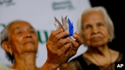 "FILE - Alleged Filipino ""comfort women"" Narcisa Claveria, 85, left, and Hilaria Bustamante, 90, display Origami paper cranes to symbolize peace during a forum to demand justice, compensation and apology from the Japanese government."