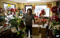 Patti Thomas prepares a flower basket for an order at her floral shop in Lula, Georgia, in Hall County, Jan. 10, 2017.