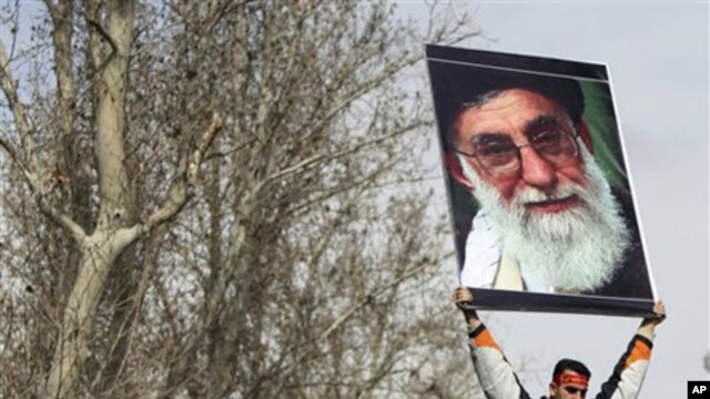 A pro-government Iranian holds a poster of supreme leader Ayatollah Ali Khamenei during the funeral ceremony of Sane Jaleh, a student who was killed during Monday's clashes, in Tehran, Iran, February 16, 2011