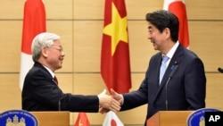 아베 신조 일본 총리(오른쪽)가 15일 일본을 처음 방문한 응웬 푸 쫑 베트남 공산당 서기장과 공동 기자회견을 가진 후 악수하고 있다.
