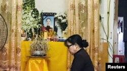 Một phụ nữ cầu khấn bên bàn thờ có hình ảnh của Phạm Thị Trà My, bị nghi nằm trong số 39 nhạn nhân chết trong xe tải ở Anh, tại nhà bà ở Hà Tĩnh hôm 27/10. Việt Nam cho biết đang đẩy nhanh việc nhận dạng quốc tịch và danh tính của các nạn nhân.