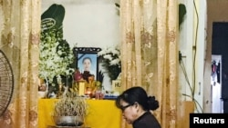 Một phụ nữ cầu nguyện trước bàn thờ có ảnh của Trà My, một trong 39 nạn nhân người Việt chết trong thùng xe tải ở Anh, tại nhà của gia đình nạn nhân ở Hà Tĩnh, ngày 27/10/2019. REUTERS/Kham
