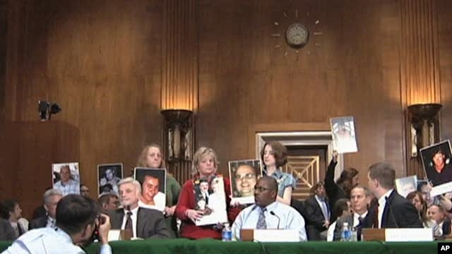 Family members hold picture of miners killed in US mining explosion at congressional hearing, 27 Apr 2010