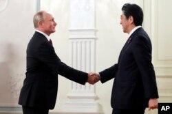블라디미르 푸틴 러시아 대통령과 아베 신조 일본 총리가 26일 모스크바 볼쇼이극장에서 열린 문화교류 행사에 앞서 악수하고 있다.