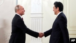Russian President Vladimir Putin, left, and Japanese Prime Minister Shinzo Abe shake hands before an opening ceremony of the cross-cultural year of Russia and Japan at the Bolshoi Theater in Moscow, Russia, May 26, 2018.
