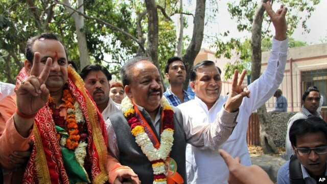 India main opposition Bharatiya Janata Party leader Harsh Vardhan, center, flashes a victory sign as he arrives with party nominee Mahesh Giri, left, to file Giri's nomination papers for the upcoming general election in New Delhi, March 20, 2014.