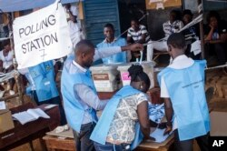 Election officials count ballot papers cast at a polling station in Freetown, Sierra Leone, March 7, 2018.