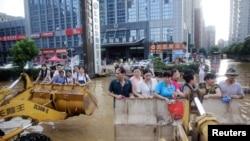 水淹武汉,人们利用挖土机前去上班(2016年7月8日)