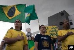 Manifestantes que apoyan la condena a prisión del expresidente Luiz Inacio Lula da Silva, cantan el himno nacional frente al Departamento de Policía de Curitiba, Brasil, donde se espera que el exmandatario se entregue. Abril 6 de 2018.