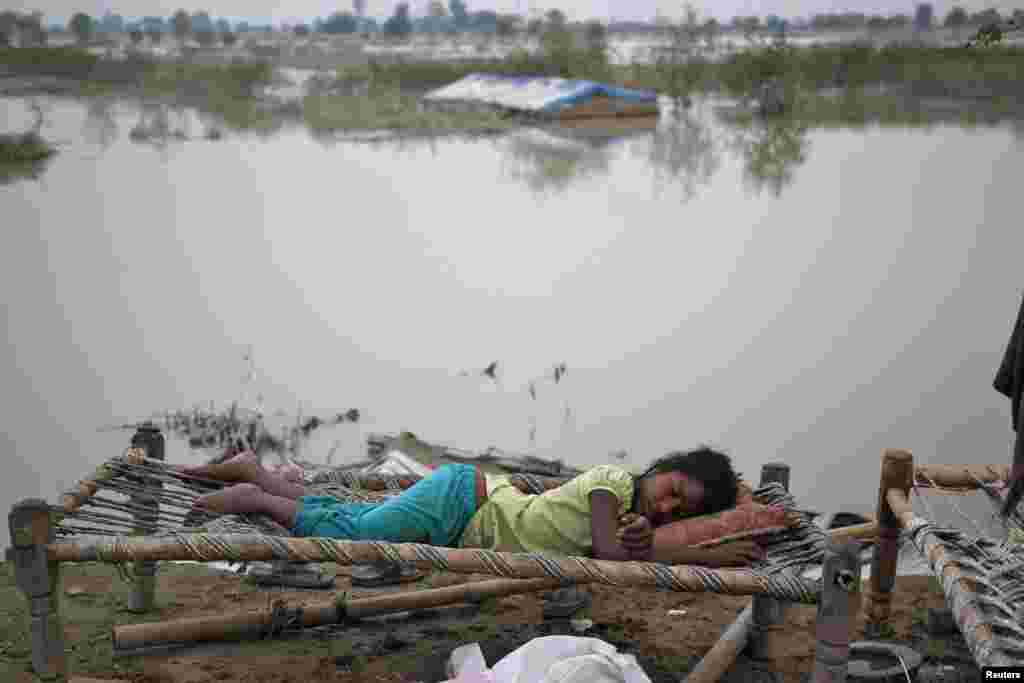 A displaced girl sleeps outside her makeshift tent at a camp by the roadside after a rise in the waters of the river Yamuna folowing heavy rains in New Delhi. India's monsoon rains could ease soon after hitting 89 percent over averages in the past week.