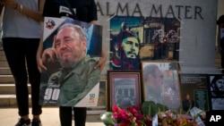 Quelques personnes tiennent des images de Fidel Castro lors d'un regroupement spontané après l'annonce de la mort du leader historique cubain à La Havane, Cuba, 26 novembre 2016.