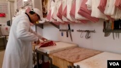 Meat is being prepared at Boucherie de l'Argonne, in Paris, Feb. 3, 2016. (L. Bryant/VOA)