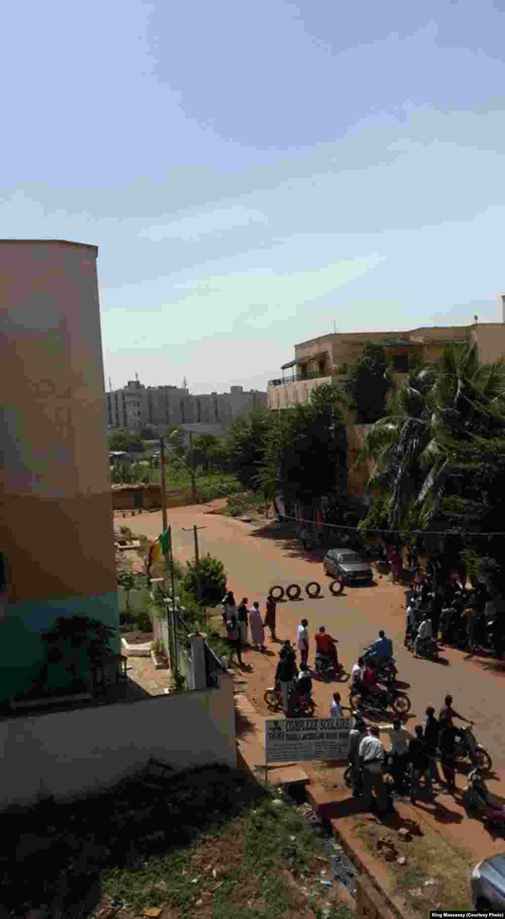 Quelques personnes dans une rue de Bamako près de l'hôtel Radisson attaqué, Mali, 20 novembre 2015. (crédit : King Massassy)