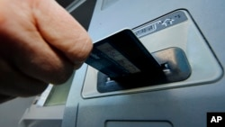 FILE - A person inserts a debit card into an ATM in Pittsburgh, Pennsylvania. The U.S. Supreme Court will allow a class action lawsuit about ATM fees to go forward.