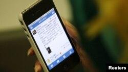 Seorang pengguna iPhone di Beijing (foto: dok). Fitur aplikasi iPhone diduga membantu pengguna mencari pekerja seks di Tiongkok.
