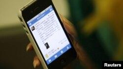 一名中國婦女在北京將微博下載到她的手機。
