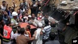 مردم و امدادگران فلسطینی در حال بیرون کشیدن پیکر بیجان یکی از جانباختگان حمله موشکی اسرائیل در غزه – ۳۰ تیر ۱۳۹۳