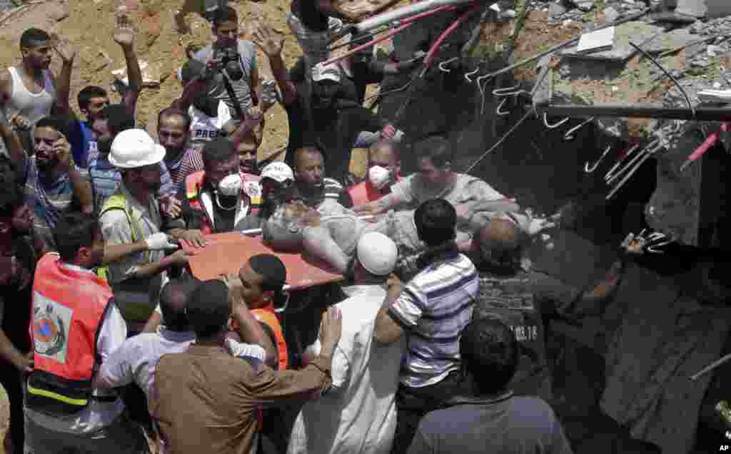 Palestinian rescue workers and civilians remove a lifeless body from the rubble of a house destroyed by an Israeli missile strike, in Gaza City, July 21, 2014.