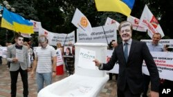 FILE - Anti-corruption activists hold a rally outside parliament in Kyiv, Ukraine, June 15, 2015. The rally organizers put a toilet seat on display as a symbol of what they feel is the effort by top officials to flush away politically inconvenient corruption cases.