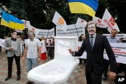 FILE - Anti-corruption activists hold a rally outside parliament in Kyiv, Ukraine, June 15, 2015. The rally organizers put a toilet seat on display as a symbol of what they felt was the effort by top officials to flush away politically inconvenient corruption cases.