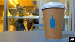 In this Thursday, Dec. 12, 2019 photo, a Blue Bottle Coffee paper to-go cup rests on a table outside one of their cafes in San Francisco. The Oakland-based chain says it's getting rid of disposable cups at two locations next year, as part of a pledge to g