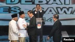 Kandidat Capres-Cawapres Prabowo Subianto-Hatta Rajasa (kiri) menyalami Joko Widodo-Jusuf Kalla sebelum acara debat di Jakarta, Senin (9/6).