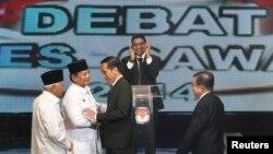 Kandidat Capres-Cawapres Prabowo Subianto-Hatta Rajasa menyalami Joko Widodo-Jusuf Kalla sebelum acara debat di Jakarta, Senin (9/6).