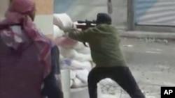 ທະຫານຂອງກຸ່ມກະບົດໃນຊີເຣຍຜູ້ນຶ່ງ ຍິງປືນຈາກແຈທາງ ໃສ່ກໍາລັງຂອງຝ່າຍລັດຖະບານ ໃນກຸງ Damascus ໃນວັນທີ 7 ທັນວາ, 2012