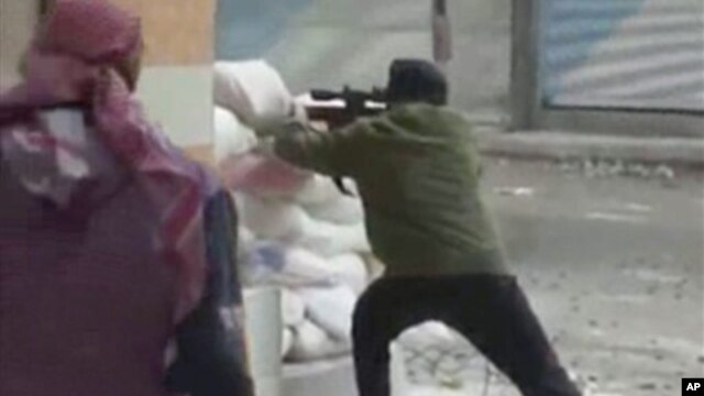 A rebel fires a weapon around a corner at Syrian government forces in Damascus, Syria, December 7, 2012.